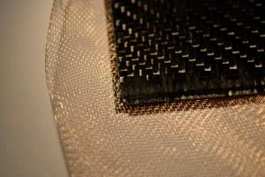 Plaque de carbone avec un issumétalliquepour réaliser un blindage électromagnétique